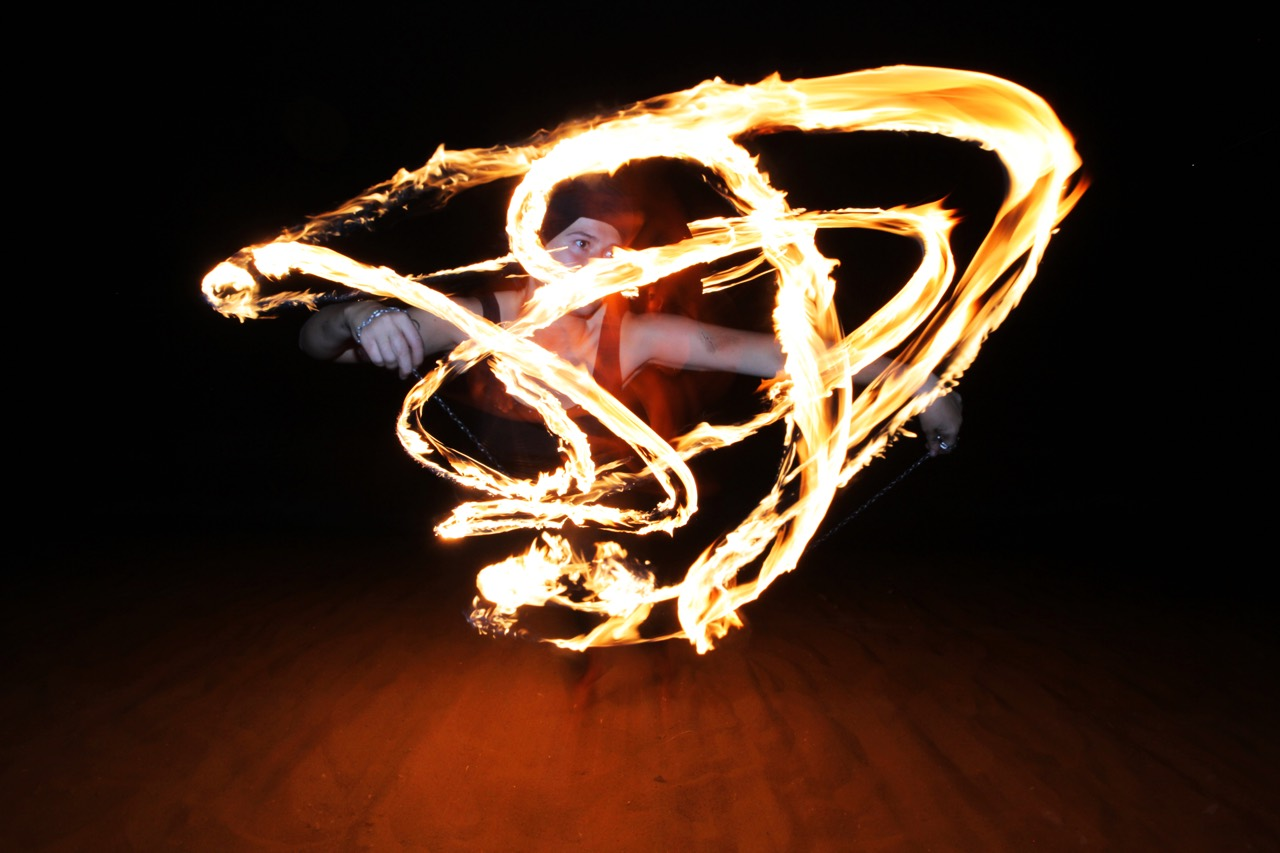 Female fire dancer surrounded by tracers